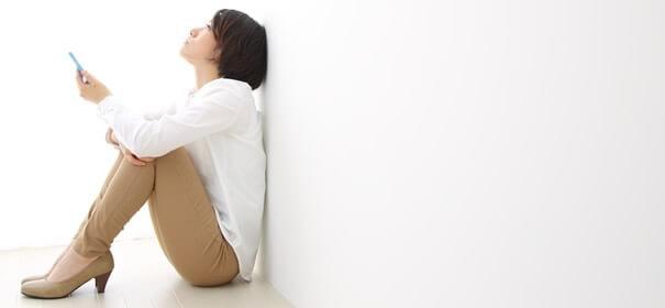 壁に寄りかかる女性の画像