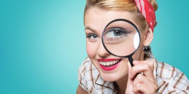 虫眼鏡を持つ女性の画像